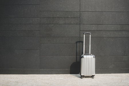 trolley suitcase of a business woman on modern wall background 版權商用圖片