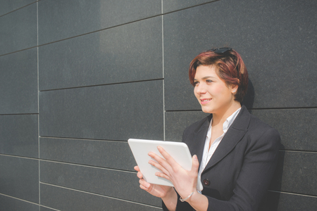 young authentic business woman with tablet pc smiling in the financial district for business trip