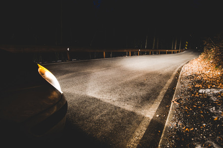 the headlights of a car on mountain road in the night - concept driving safety
