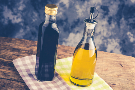 olive oil bottle and balsamic vinegar on rustic table - italian food concept
