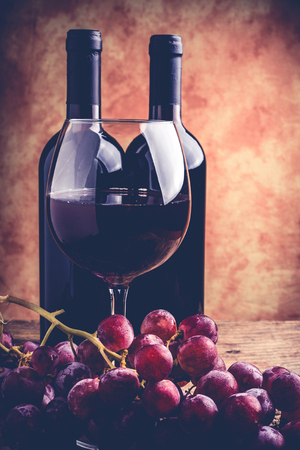 red wine glass grapes and bottle - fine wine tasting concept