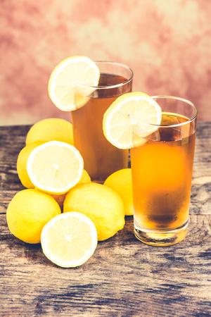 lemon ice tea on wooden table with lemons around 版權商用圖片