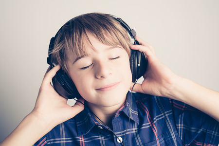 little boy with headphone listening music -  filtered retro style photo