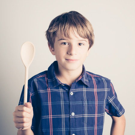 little boy with wooden spoon ready to cook -  filtered retro style