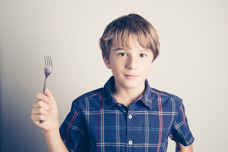 little boy with fork ready to eat - filtered retro style 版權商用圖片