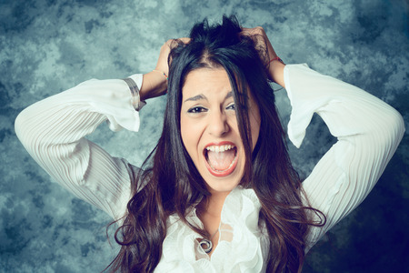 desperate mediterranean young woman with long brown hair - face expressions - filtered vintage style 版權商用圖片