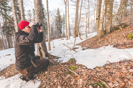 man with binoculars in the forest - outdoor activity italian Alps Italy