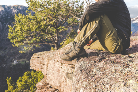hiker standing on the rocks and contemplates a beautiful mountain landscape -wanderlust travel concept with sporty people at excursion in wild nature - outdoor activity italian Alps Italy Banco de Imagens