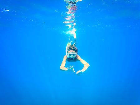 teenager having fun in the sea underwater - summertime - Sicily mediterranean sea