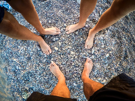 feet of teenagers sons and father on the beach to the sea - summertime - Sicily mediterranean sea