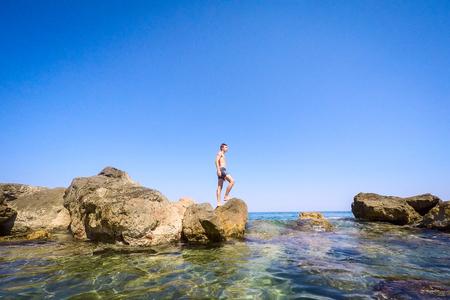 少年站在海邊的岩石上 - 夏季 - 西西里島地中海 版權商用圖片
