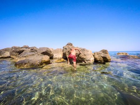 少年在海邊的岩石上 - 夏季 - 西西里島地中海 版權商用圖片