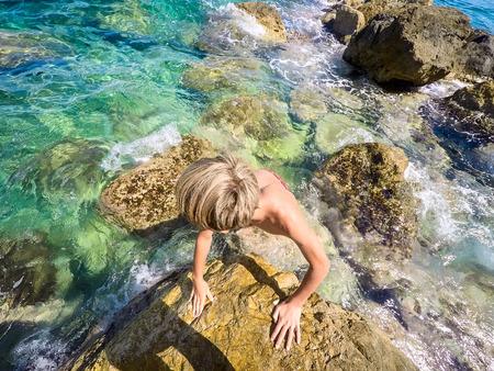 teenagers on the rocks at seaside - summertime - Sicily mediterranean sea