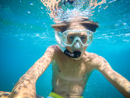 teenager having fun in the sea underwater - summertime - Sicily mediterranean sea