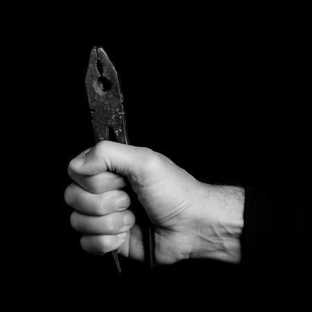 nipper - tools in a mans hand - black and white photo