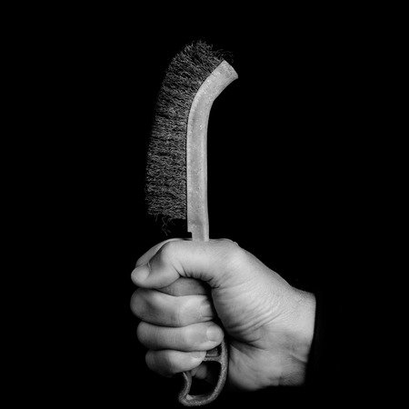 metal brush - tools in a mans hand - black and white photo 版權商用圖片