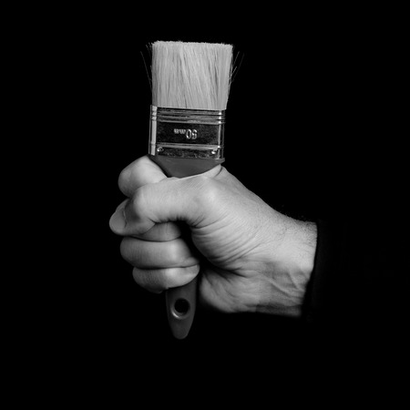 paintbrush - tools in a mans hand - black and white photo