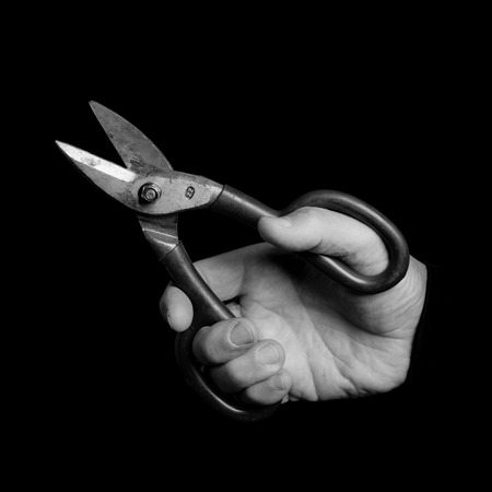 metal scissors - tools in a mans hand - black and white photo