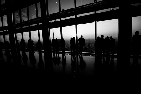 people watch the city from above at panoramic place - black and white image 版權商用圖片