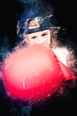young boy fighter with boxing gloves on black background
