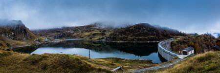 panoramic view of a dam lake in mountain in a cludy day