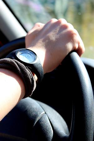 weaker: Detail of female hand on the steering wheel of a car