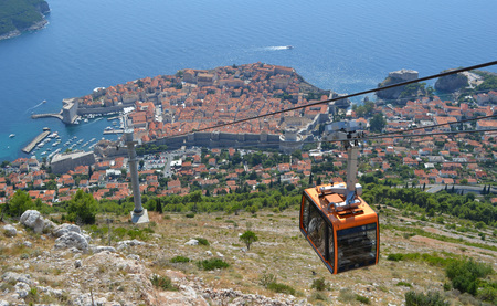 srd: Dubrovnik Cable Car takes tourists from the old town to the top of Mount Srd. Old town city wall and the Adriatic sea in background.