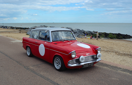 Classic Red Ford Anglia in vintage car rally on Felixstowe seafront.