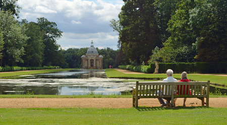 wrest: People on bench admiring the view of the Thomas Archer pavilion at Wrest park.