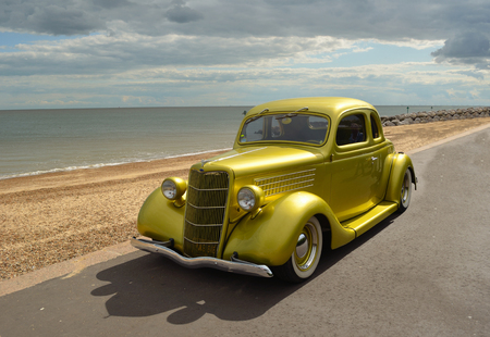 felixstowe: Classic Gold Ford  vintage car in rally on Felixstowe seafront.