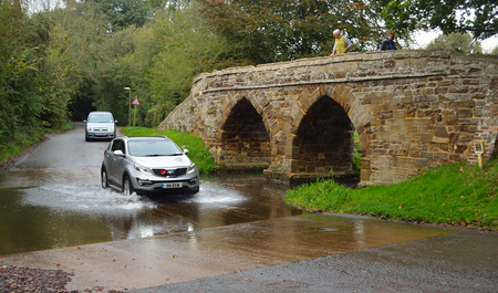 old packhorse bridge: Car being driven through Sutton Splash with people on ancient packhorse bridge.