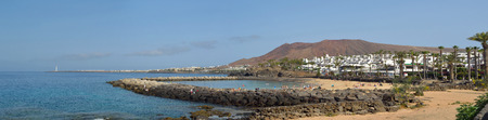 Panorama of the western end of Playa Blanca promenade with holiday makers on the man made Flamingo beach and the lighthouse.