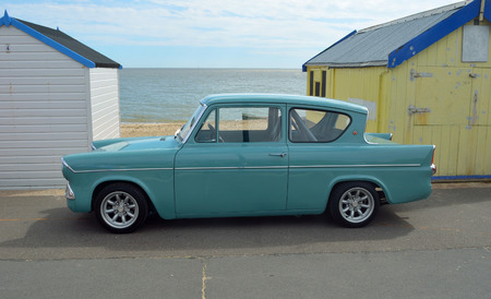 Classic blue Ford Anglia by beach huts on Felixstowe promenade.