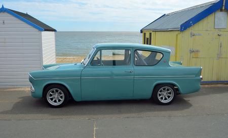 felixstowe: Classic blue Ford Anglia by beach huts on Felixstowe promenade.