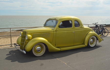 felixstowe: Classic Gold Ford vintage car in rally on Felixstowe seafront. Editorial