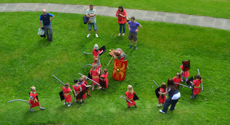 Children pretending to be Roman Soldiers being watched by adults at Chester.