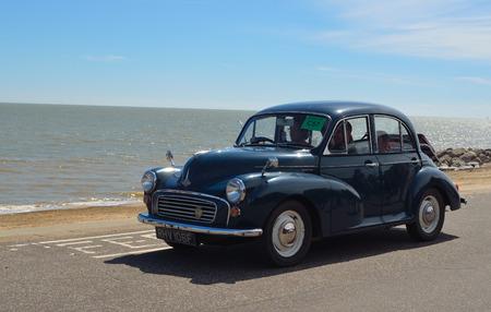 felixstowe: Classic Blue Morris Minor 1000 being driven along Felixstowe seafront promenade.