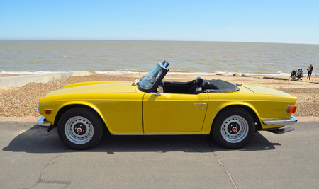 Classic Yellow Triumph TR6 on the seafront at Felixstowe. Editorial