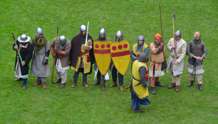 Medieval men at arms being drilled by knight.