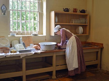Victorian Kitchen maid washing dishes in sink.