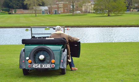 morris: A Vintage Morris Minor motor car parked near water with driver.