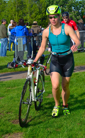 triathlete: Female triathlete at end of cycling stage with bicycle.