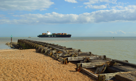 felixstowe: A small Container ship entering the Port of Felixstowe being guided by tug, old breakwater in foreground.