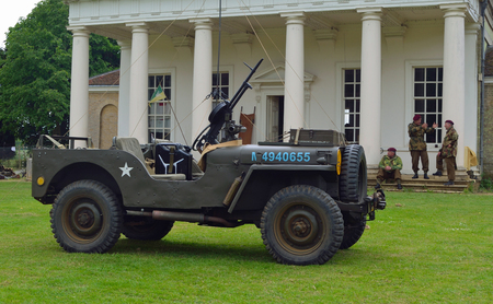 berets: World War 2 Jeep mounted Machine gun men in ww2 military uniforms with red berets in front of old building. Editorial