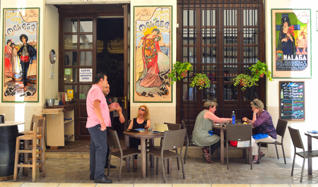 spainish: Spainish tapas Bar with colourful ceramic tiles on walls, customers enjoying lunch.