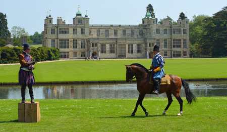 Two men in Elizabethan costume one on a horse in front of stately home.