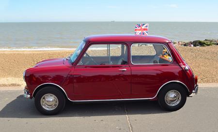 felixstowe: Classic Red Austin Mini motor car parked on  Felixstowe seafront promenade.