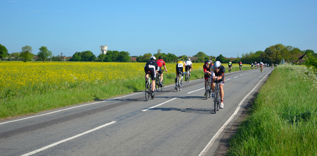 cambridgeshire: Triathletes on road cycling stage of triathlon riding in both directions.