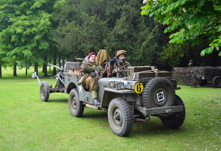 : World War 2 Jeep with men dressed as World War 2 Soldiers, towing Gun. Editorial