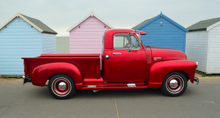 Classic Red  Chevrolet 3100 pickup truck on seafront promenade in front of beach huts. Editorial